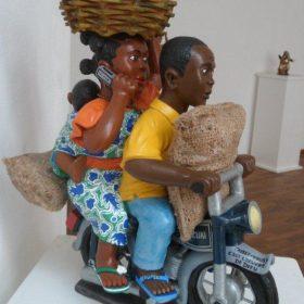 Sculpture - Euloge Glélé - Homme et femme sur mobylette - sacs - panier de pommes - enfant à l'arrière
