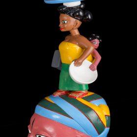 Sculpture - masque gèlèdè - Wabi DOSSOU -femme africaine avec haut jaune et jupe verte - assiette de tomates rouges sur la tête - enfant sur le dos - tient une assiette et un tabouret - visage rosé, bleu, vert, jaune - marqué sur le front et la joue