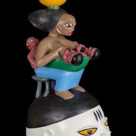 Sculpture - masque gèlèdè - Kifouli DOSSOU - femme africaine assise donnant le sein à ses enfants - jupe bleu - pot jaune sur sa tête - tabouret gris - visage blanc, noir, bleu