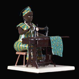 Sculpture - Didier AHADJI - Femme africaine - Couturière - tenue traditionnelle bleue et jaune - machine à coudre marron - tissu bleu à motifs oiseaux sur branches d'arbre